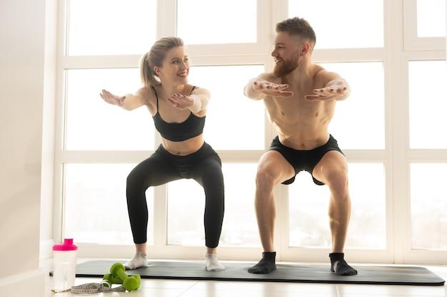 웃는 운동가와 운동가는 피트 니스 매트에 앉는다. 금발의 여자는 운동복을 입는다. 벌거 벗은 몸통을 가진 수염 난 남자. 집에서 스포츠 활동의 개념입니다. 넓은 햇볕이 잘 드는 아파트의 인테리어