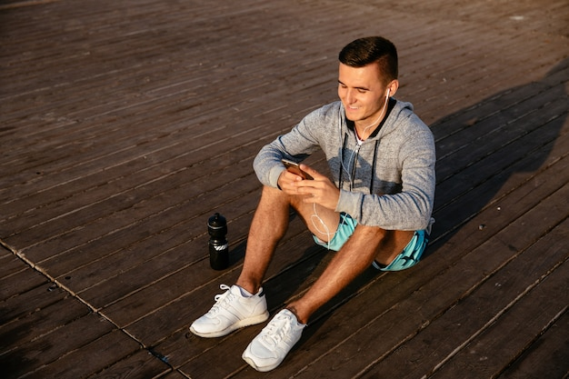 Smiling sportsman in earphones, listening to music, while using a mobile phone