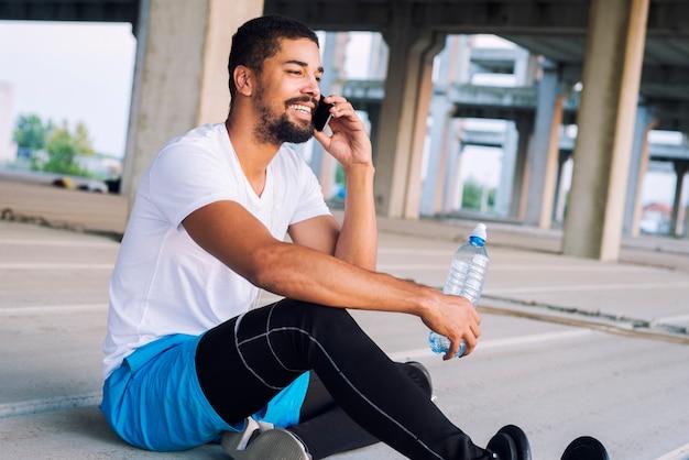 Улыбающийся спортсмен закончил тренировку в тренажерном зале, отдыхая, используя мобильный телефон