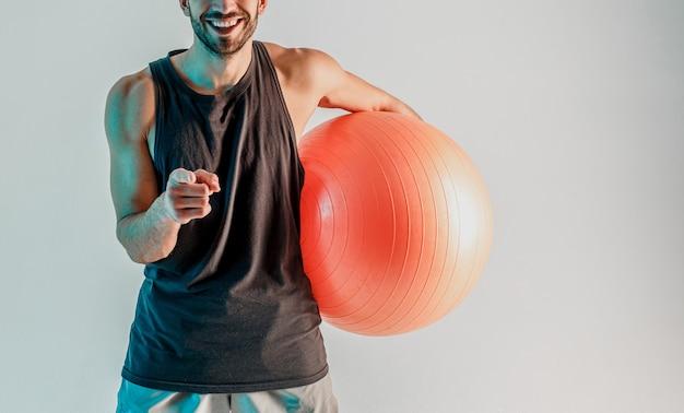 웃고 있는 스포츠맨이 피트니스 공을 잡고 손가락으로 카메라를 가리키고 있습니다.