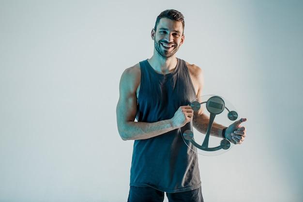 笑顔のスポーツマンは体重計を持っています。若いひげを生やしたヨーロッパ人はスポーツユニフォームを着て、カメラを見ています。ターコイズブルーの背景に分離。スタジオ撮影。コピースペース