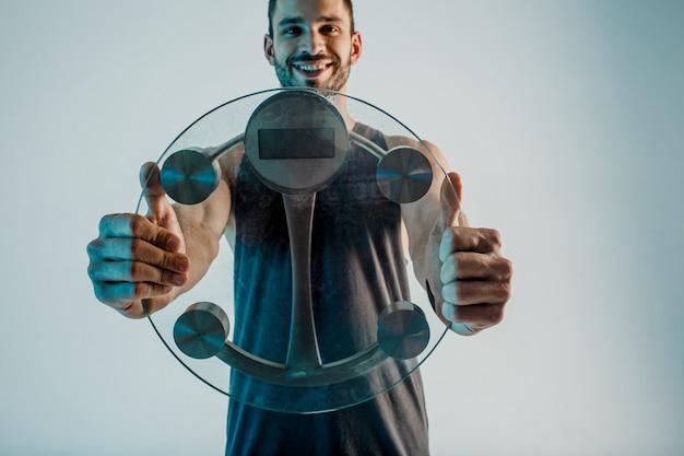 カメラに体重計を示す笑顔のスポーツマン。若いひげを生やしたヨーロッパ人はスポーツユニフォームを着ています。ターコイズブルーの光で灰色の背景に分離。スタジオ撮影。コピースペース
