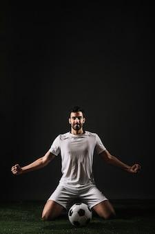 Smiling sportsman sitting near ball