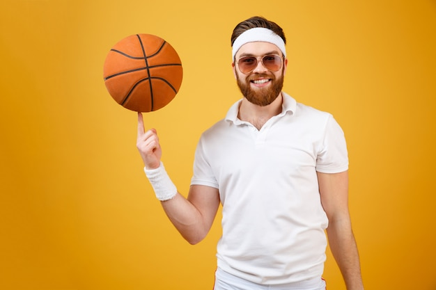 Smiling sportsman in sunglasses holding basketball on finger