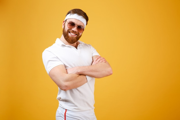 Smiling sportsman in sunglasses with crossed arms
