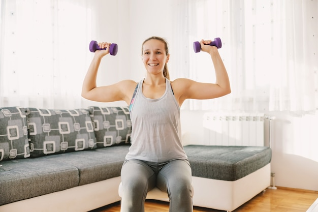 Smiling sportswoman sitting on the chair in her apartment and doing exercises for biceps. if you can't go to the gym you can make your own at home.
