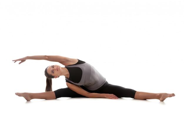 Smiling sportswoman stretching her body