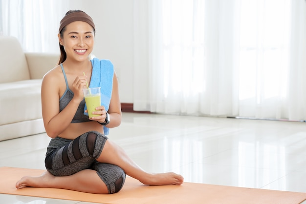 Smiling sportswoman with glass of smoothie