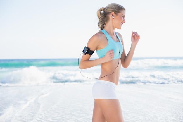 Smiling sporty blonde in sportswear jogging