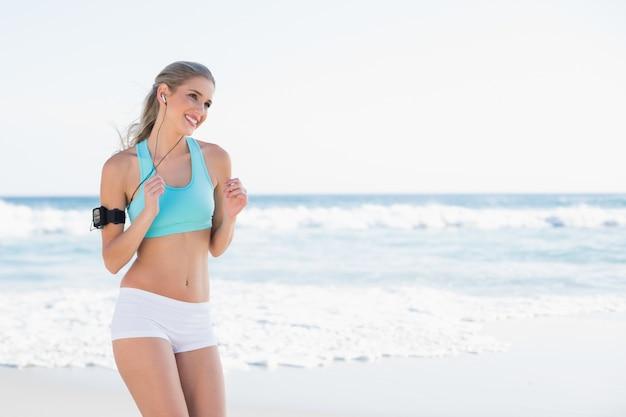 Smiling sporty blonde in sportswear running