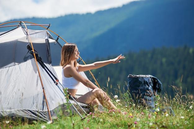 Улыбающаяся спортивная девушка-рюкзаком сидит у входа в палатку возле рюкзака и треккинговой палки, указывая на что-то вдалеке, наслаждаясь солнечным утром в горах