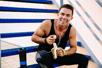 Smiling sporty guy in earphones, eating a banana, after workout, sitting on stairs