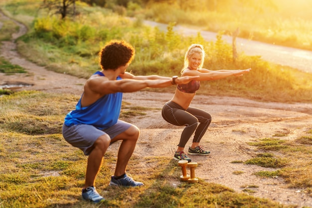 Smiling sporty muscular couple in sportswear doing endurance in squatting position in nature on sunny summer day.