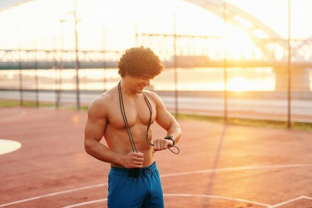Улыбающийся спортивный человек без рубашки с веревкой на шее, глядя на умные часы, стоя на площадке утром