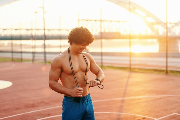 Smiling sporty shirtless man with rope around neck looking at smart watch while standing on the court in the morning