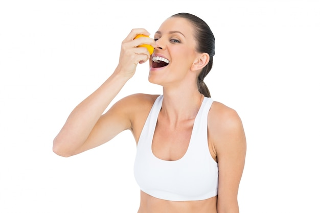 Smiling sporty woman drinking juice from orange
