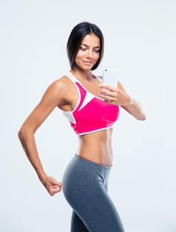 Smiling sporty woman making selfie photo