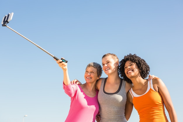 Smiling sporty women taking selfies with selfiestick