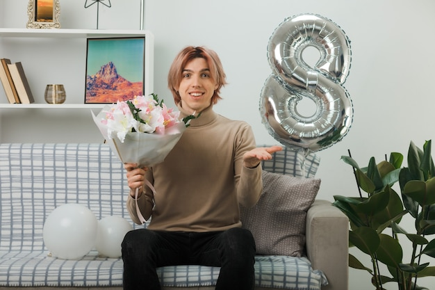 Smiling spreading hand handsome guy on happy women day holding bouquet sitting on sofa in living room