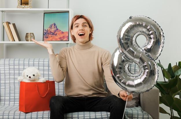 リビングルームのソファに座って8番の風船を持って幸せな女性の日に笑顔の広がり手ハンサムな男