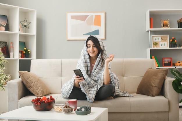 Улыбаясь, раскинув руки, молодая девушка, завернутая в плед, держит и смотрит в телефон, сидя на диване за журнальным столиком в гостиной