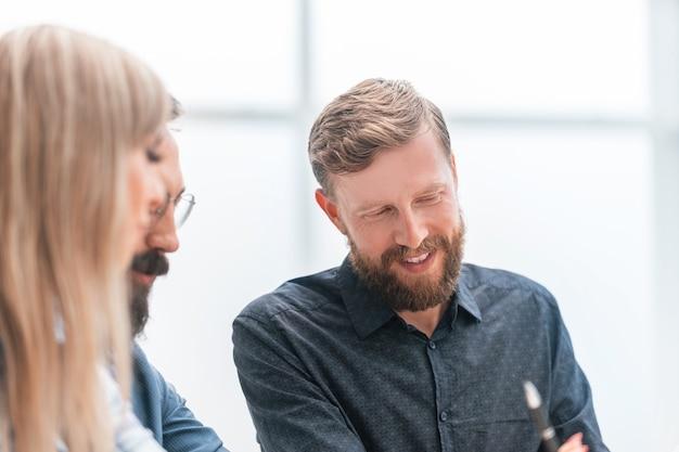 Улыбающийся персонал обсуждает финансовые документы на встрече. бизнес-концепция