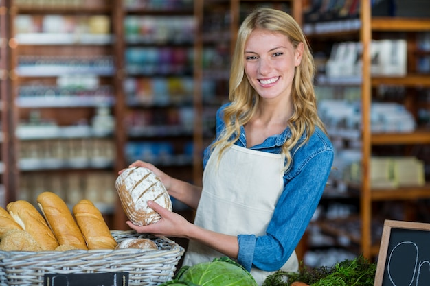Smiling staff holding bread in organic section