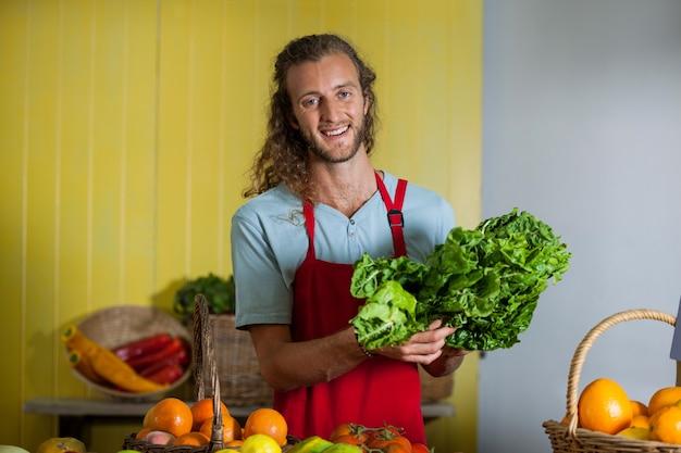 市場のカウンターで緑豊かな野菜を持って笑顔のスタッフ