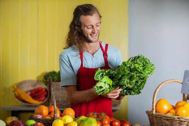 カウンターで葉物野菜を見て笑顔のスタッフ