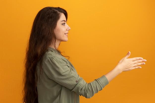 Улыбаясь, стоя в профиль, молодая красивая девушка в оливково-зеленой футболке, протягивая руку сбоку, изолированную на желтой стене
