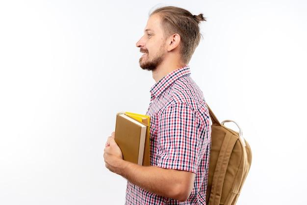 책을 들고 배낭을 입고 프로필 보기에 서 있는 미소 젊은 남자 학생