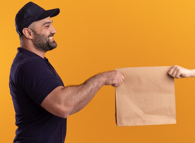 Smiling standing in profile view middle-aged delivery man in uniform and cap giving paper food package to client isolated on yellow wall