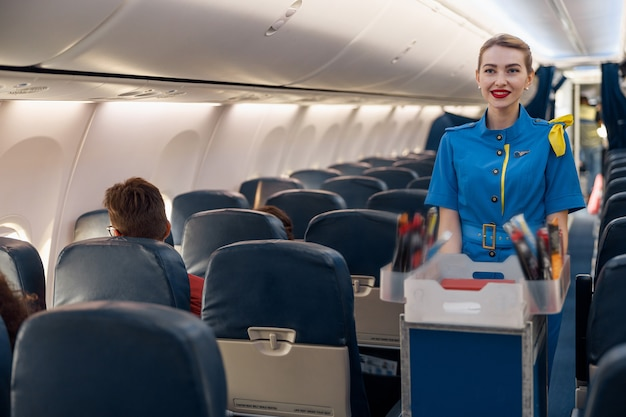 Smiling stewardess serving food to passengers on aircraft. air hostess walking with trolley on aisle. travel, service, transportation, airplane concept