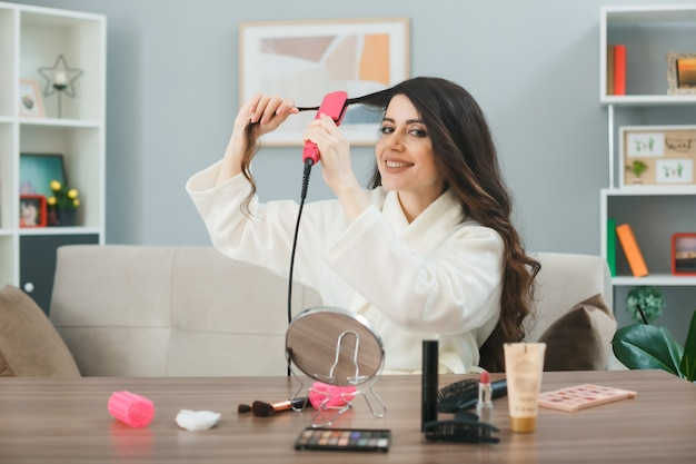 Smiling straighten hair with flat iron young girl sitting at table with makeup tools in living room
