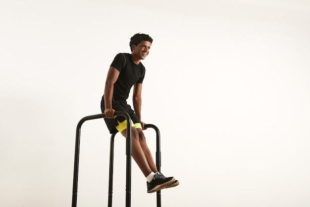 Smiling strong african american athlete with an afro wearing black synthetic shirt and black and yellow shorts doing l-sits on short bars at home isolated on white.