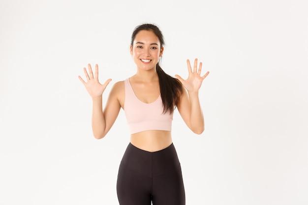 강하고 날씬한 아시아 여성 피트니스 강사 교육 강의 미소, 완벽한 몸매와 생산적인 운동을위한 10 단계 설명