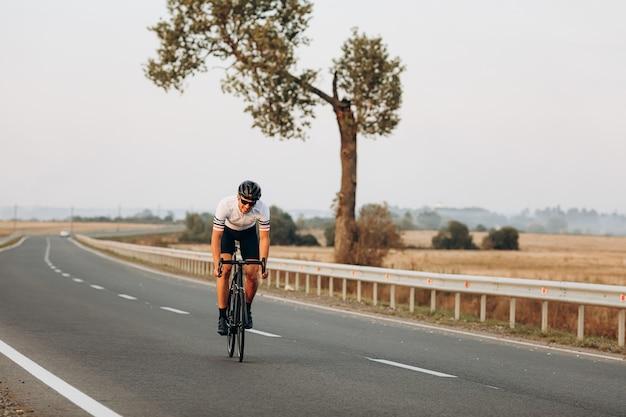 屋外で黒い自転車でスポーツ活動を楽しんでいる強いサイクリストの笑顔