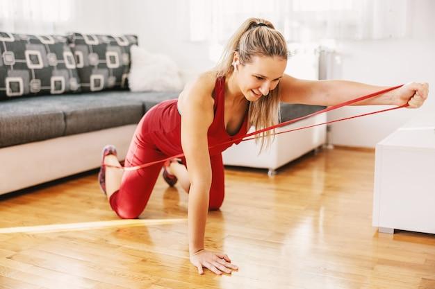 Улыбающаяся сильная спортсменка стоит на коленях на полу и растягивает силовую резину.