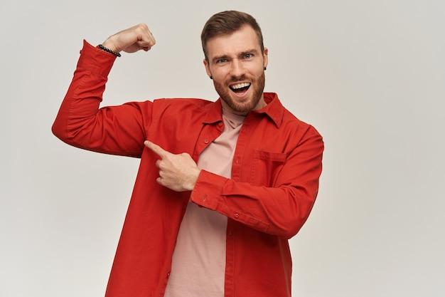 빨간 셔츠에 웃는 강한 젊은 수염 난 남자는 자신감이 있고 흰 벽 위에 그의 팔뚝을 가리키는 것처럼 보입니다.