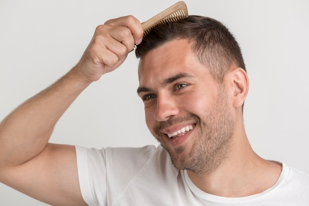 Smiling stubble man comb his hair against white backdrop