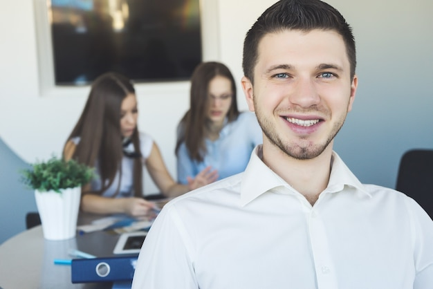 Smiling student close up portrait with working team of classmates on the background