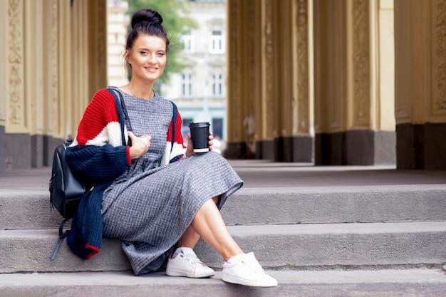 Усмехаясь девушка студента сидит на внешней лестнице и держит бумажный стаканчик.