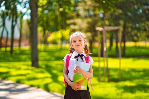 Улыбающаяся студентка в школьном рюкзаке и с ноутбуком