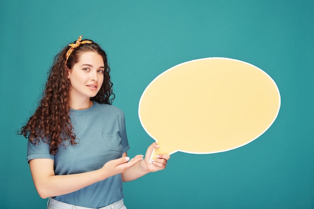 青い壁にプレゼンテーションをしながら吹き出しバナーを保持している巻き毛の学生の女の子の笑顔