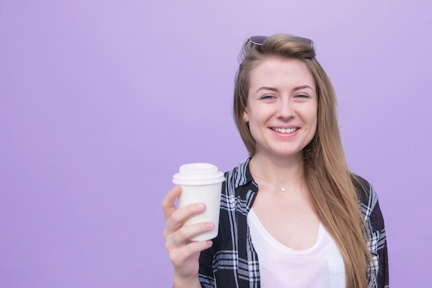 Smiling student girl with a glass of coffee in his hands is isolated on a purple background.