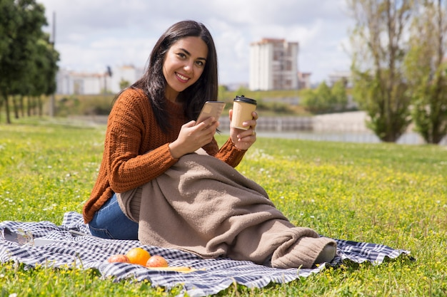 Smiling student girl wrapped in plaid drinking coffee