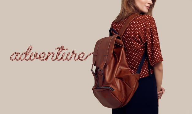 Smiling student hipster woman with backpack going on a vacation