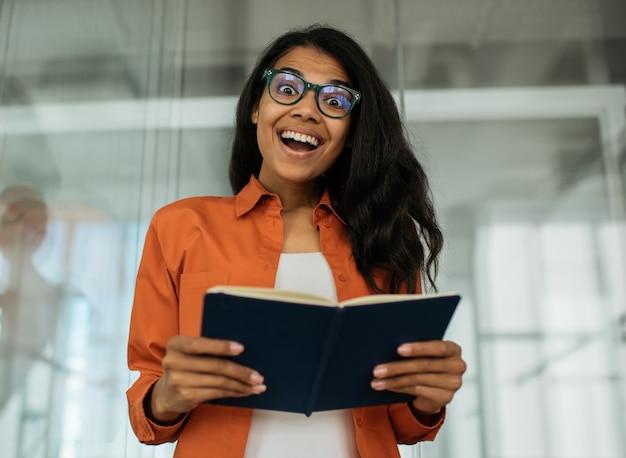 学習言語教育の概念を勉強している本を持っている笑顔の学生