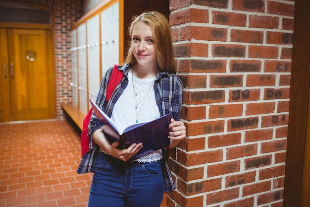 Smiling student studying leaning against the wall