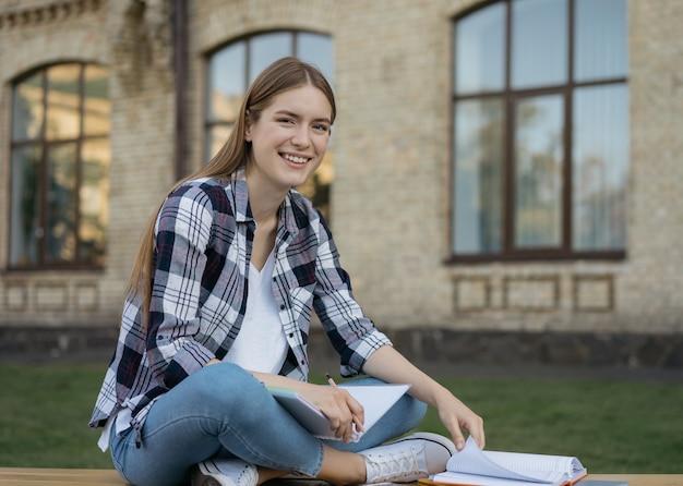 大学のキャンパスに座って言語を学ぶことを勉強している笑顔の学生